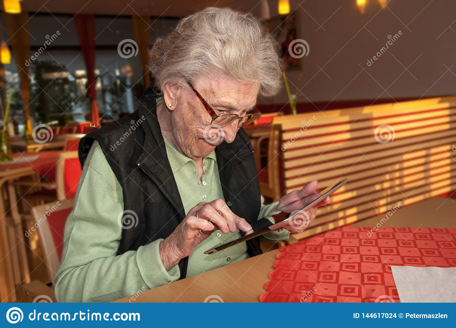 Senior woman looking at screen of tablet computer