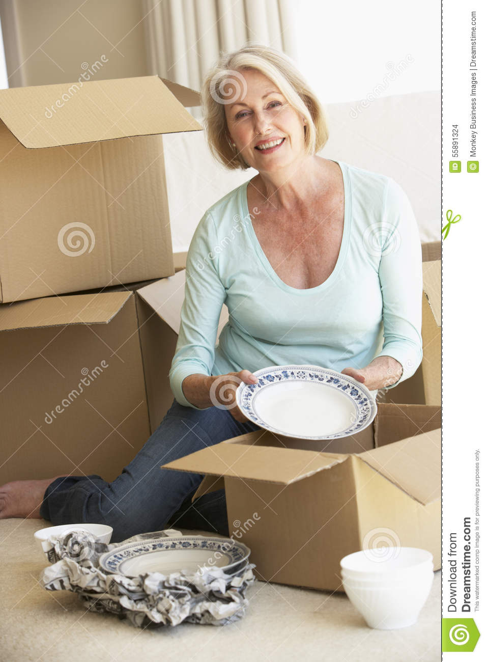 Senior Woman Moving Home And Packing Boxes Stock Photo