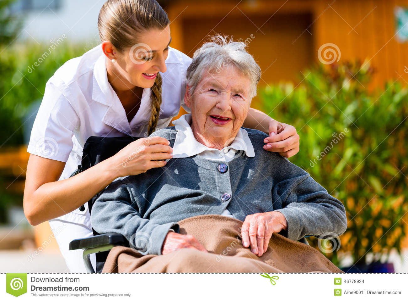 senior woman in nursing home with nurse in garden stock