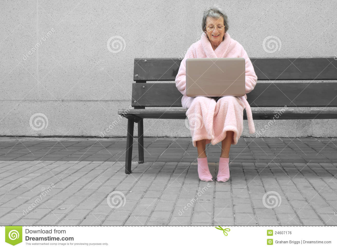 Senior woman in pink robe outdoors with laptop