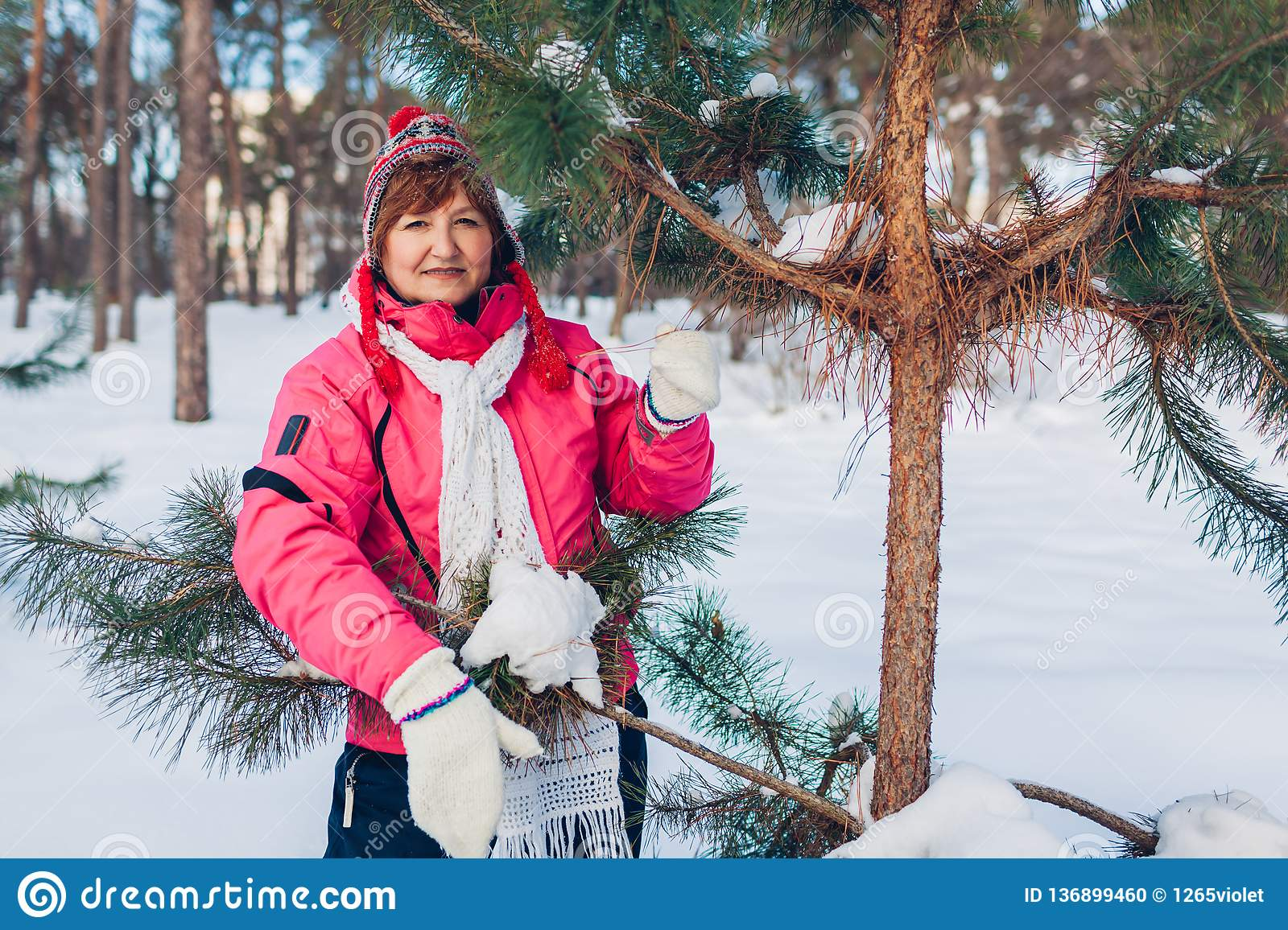 Senior woman posing by fir tree at sunny winter day in the forest
