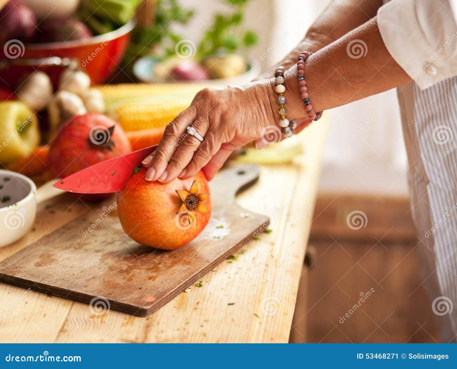 Senior woman preparing fruit salad