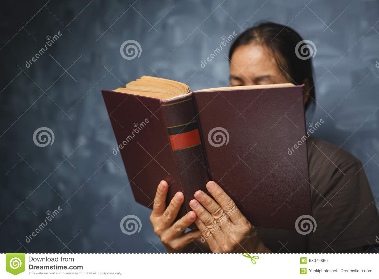 Senior Woman Reading A Book At Living Room With Old Vintage Tabl