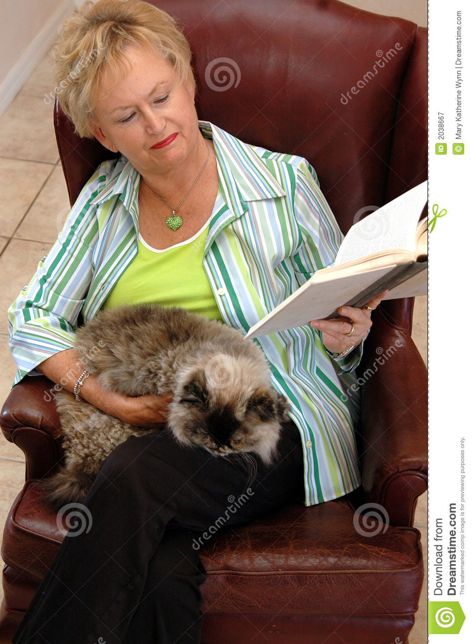 Senior woman reading with cat