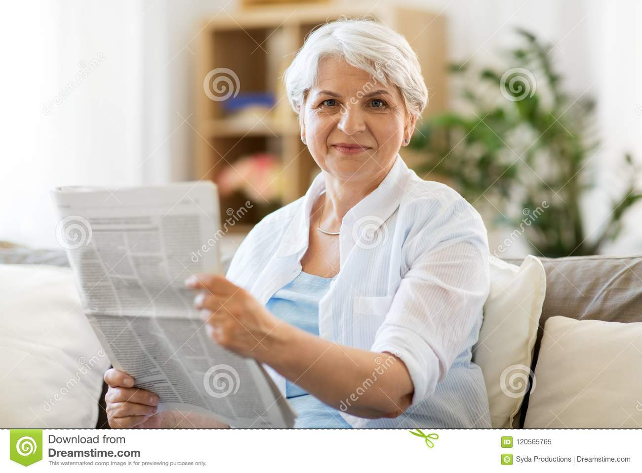 senior woman reading newspaper at home stock image - image of