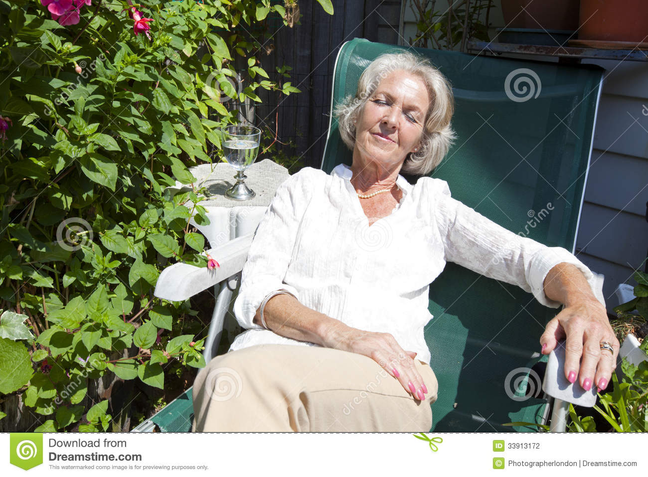 Senior Woman Relaxing On Lounge Chair In Garden Stock
