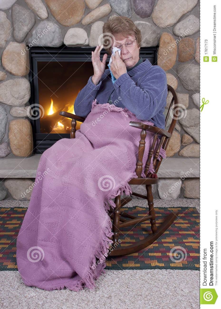 Mature senior woman cries while sitting in her rocking chair by a fire ...