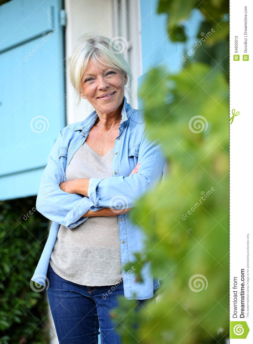 Senior woman standing in front of home