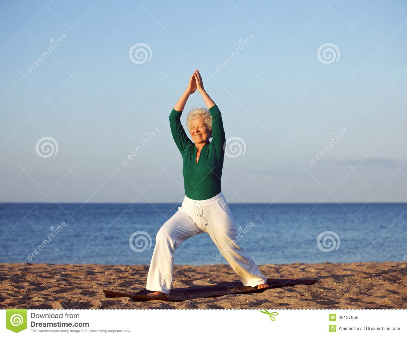 Senior Woman Stretching Against Beach Background Royalty