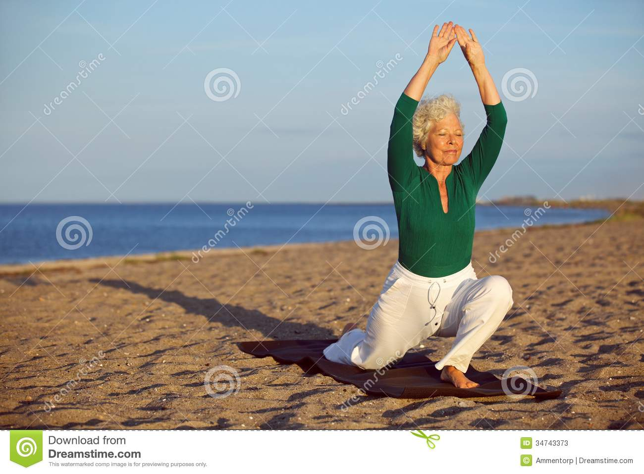 Senior woman stretching on the beachYoga Poses On The Beach