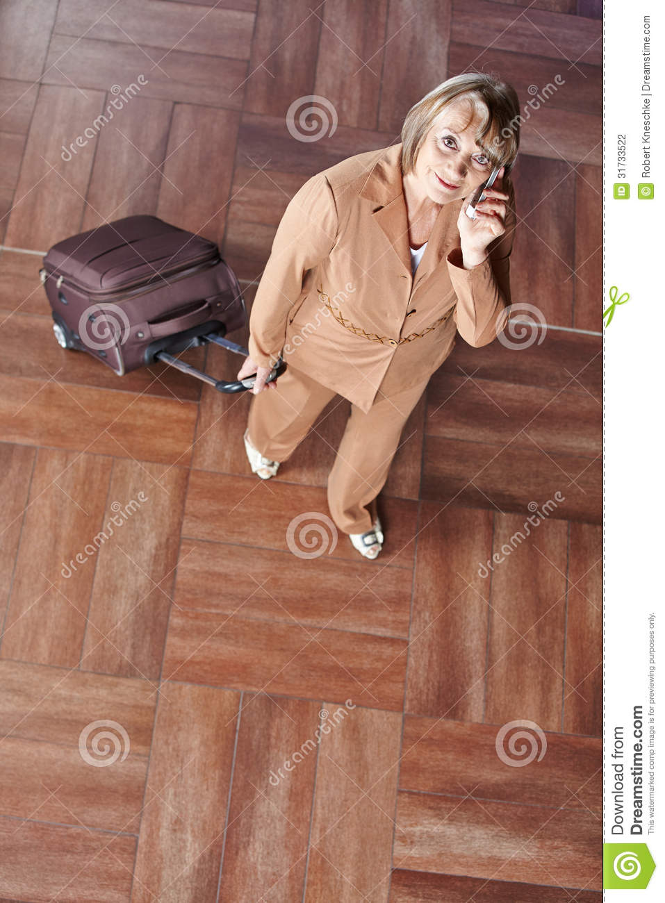 Senior woman with suitcase making phone call