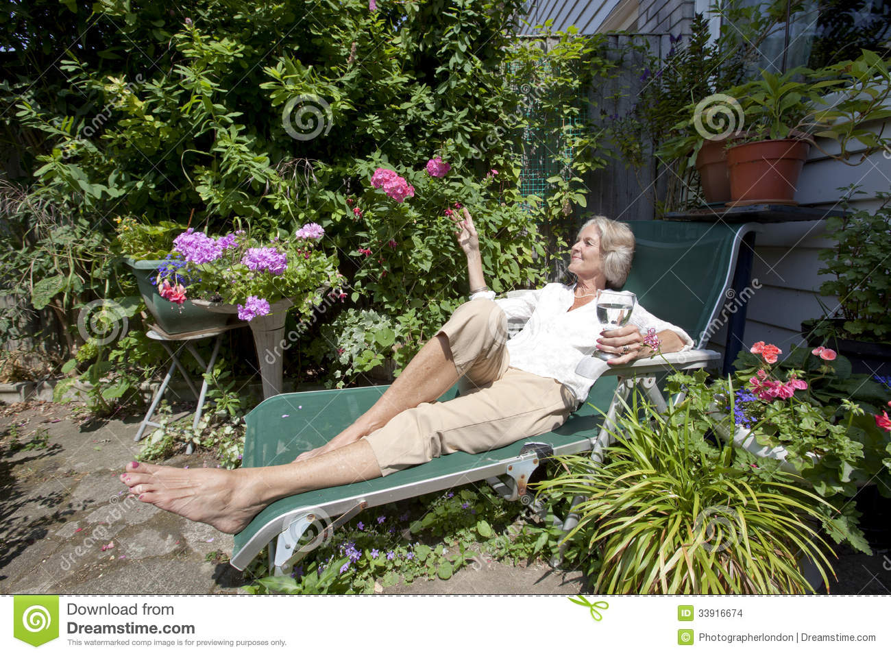 Senior Woman With Wineglass Relaxing Lounge Chair In Garden Stock Image