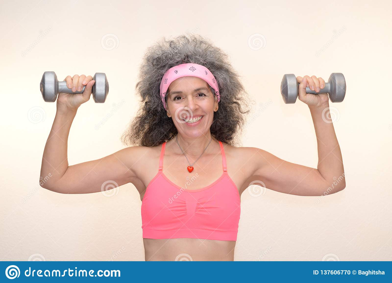 A Smiling Woman Over Fifty In Gym Outfit Is Holding Up Dumbbells Bandana Sweatband Grey Hair Plain Background