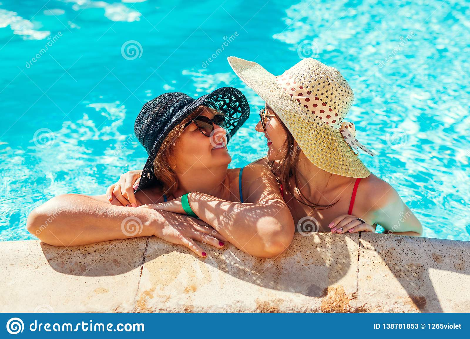 Senior woman relaxing with her adult daughter in hotel swimming pool. People enjoying vacation. Mother`s day