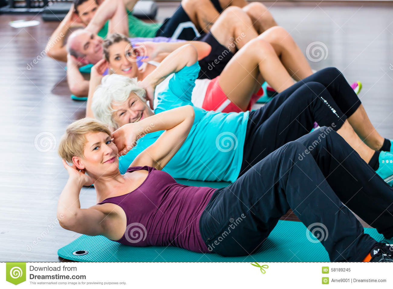 Senior and young people doing sit-up in fitness gym