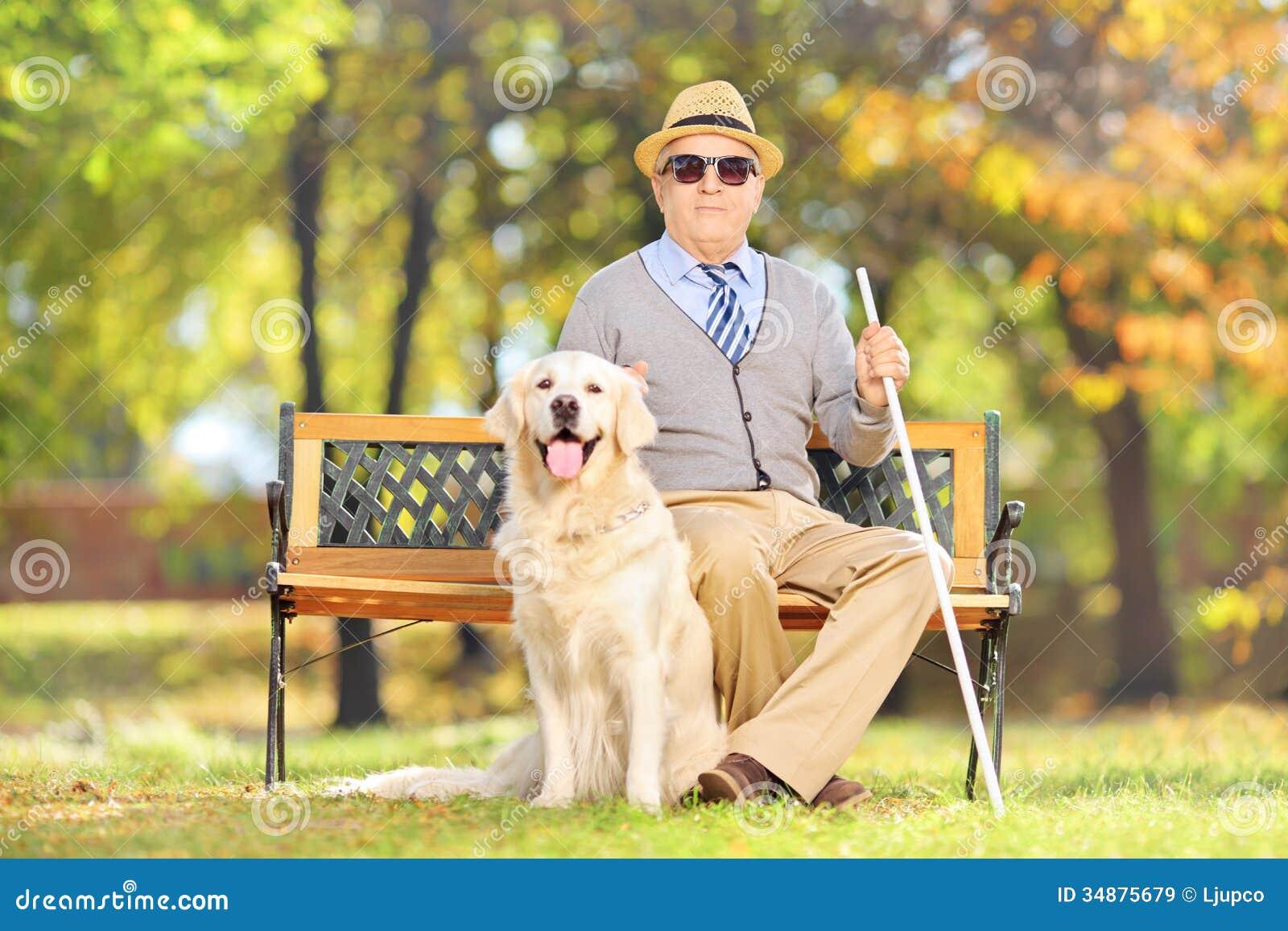 Seniora dżentelmenu niewidomy obsiadanie na ławce z jego psem w normie,