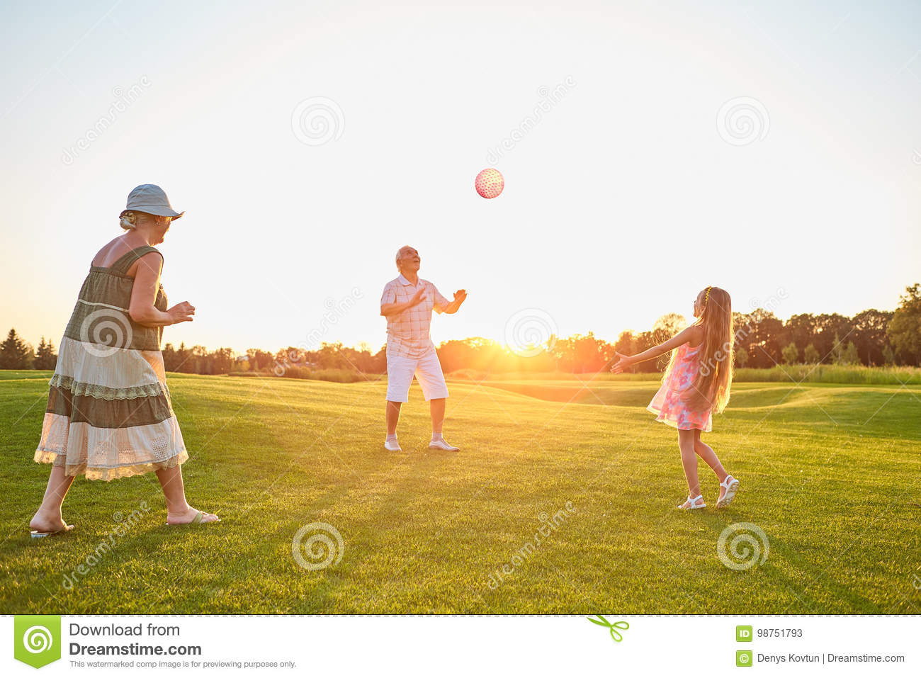 Seniors with child playing ball.