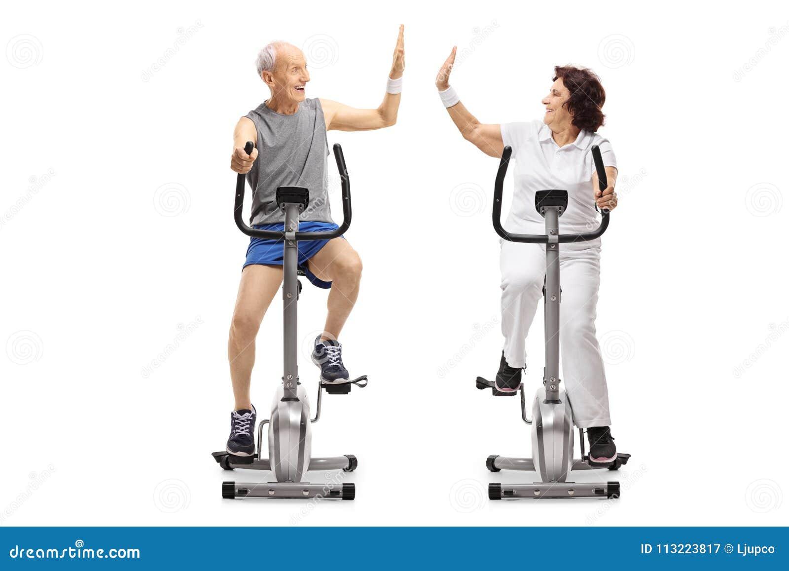 Seniors on exercise bikes high-fiving each other