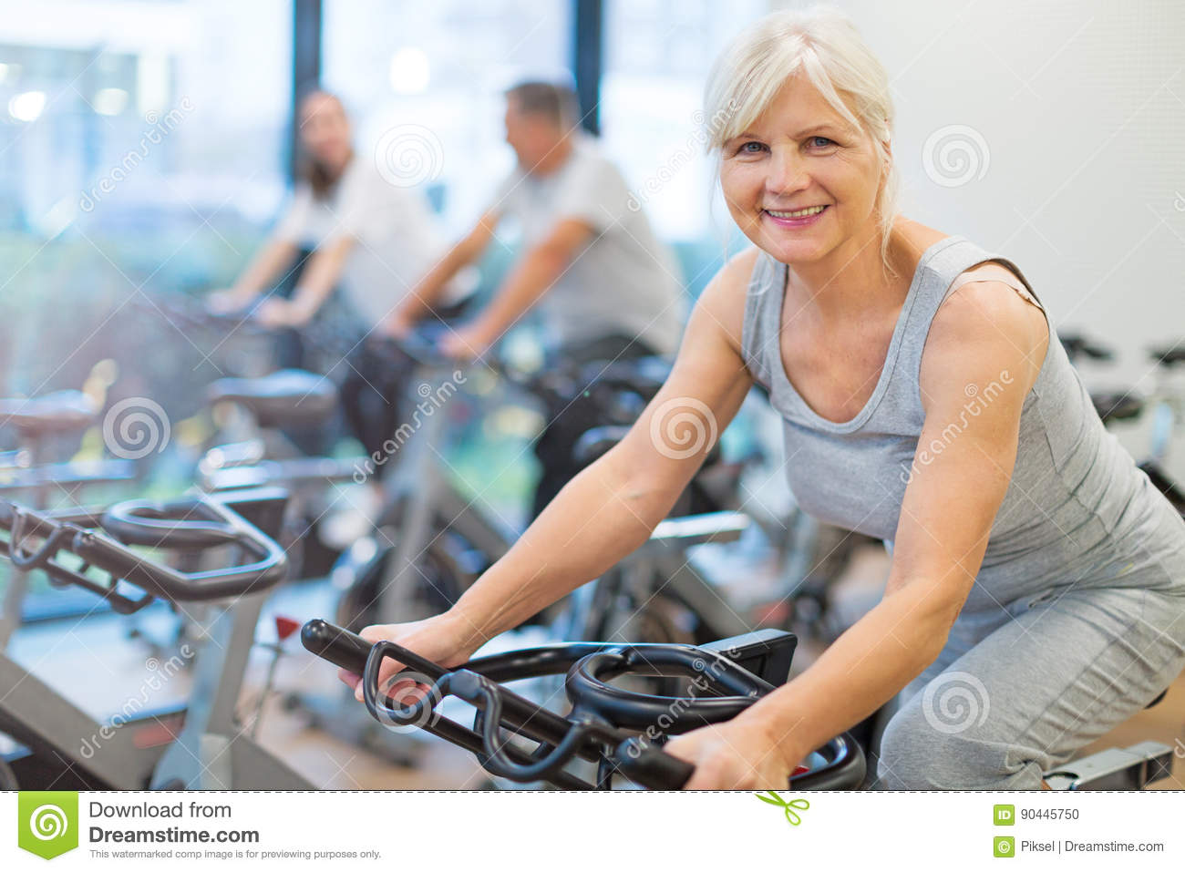 Seniors on exercise bikes in spinning class at gym
