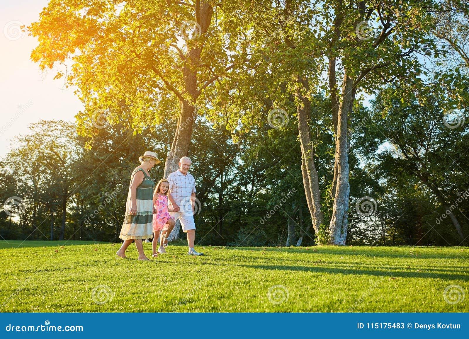 Seniors with grandchild walking outdoors.