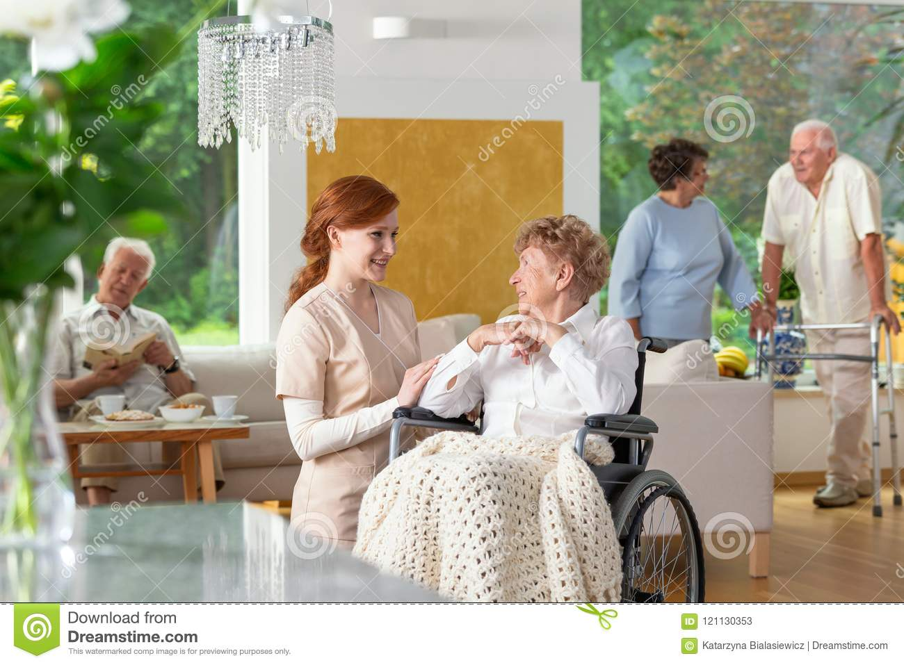 Seniors in a luxury living room of a private retirement home. Te