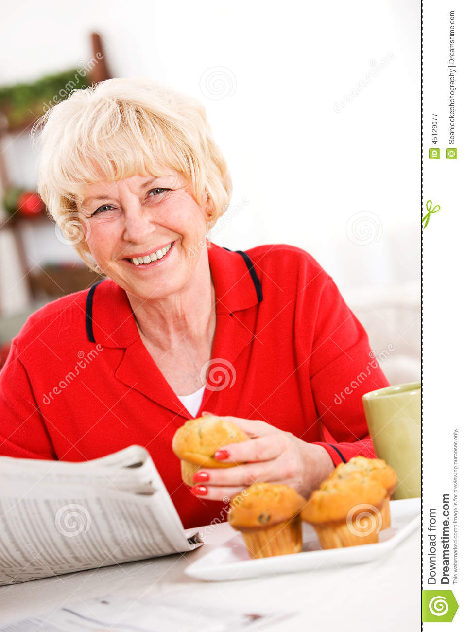 Seniors: Woman Having A Muffin and Newspaper