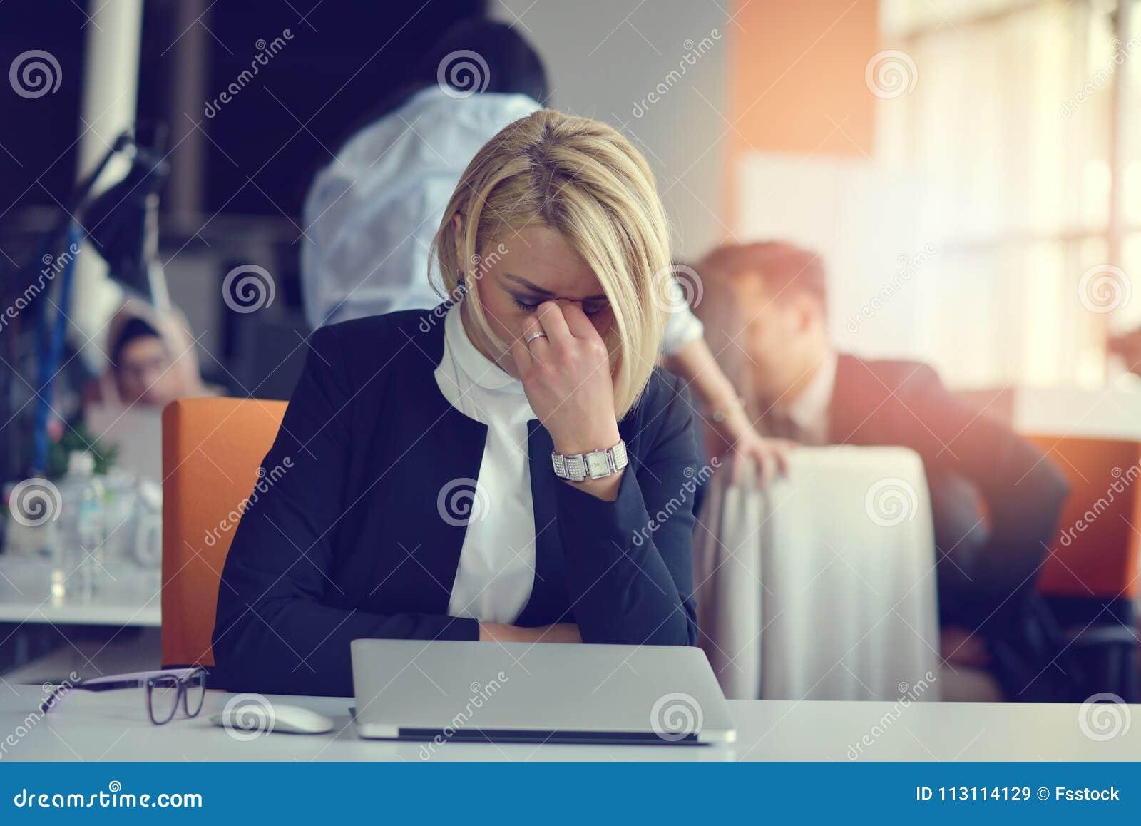 Sensación cansado y subrayado La mujer adulta frustrada que guardaba ojos se cerró de cansancio mientras que se sentaba en oficin