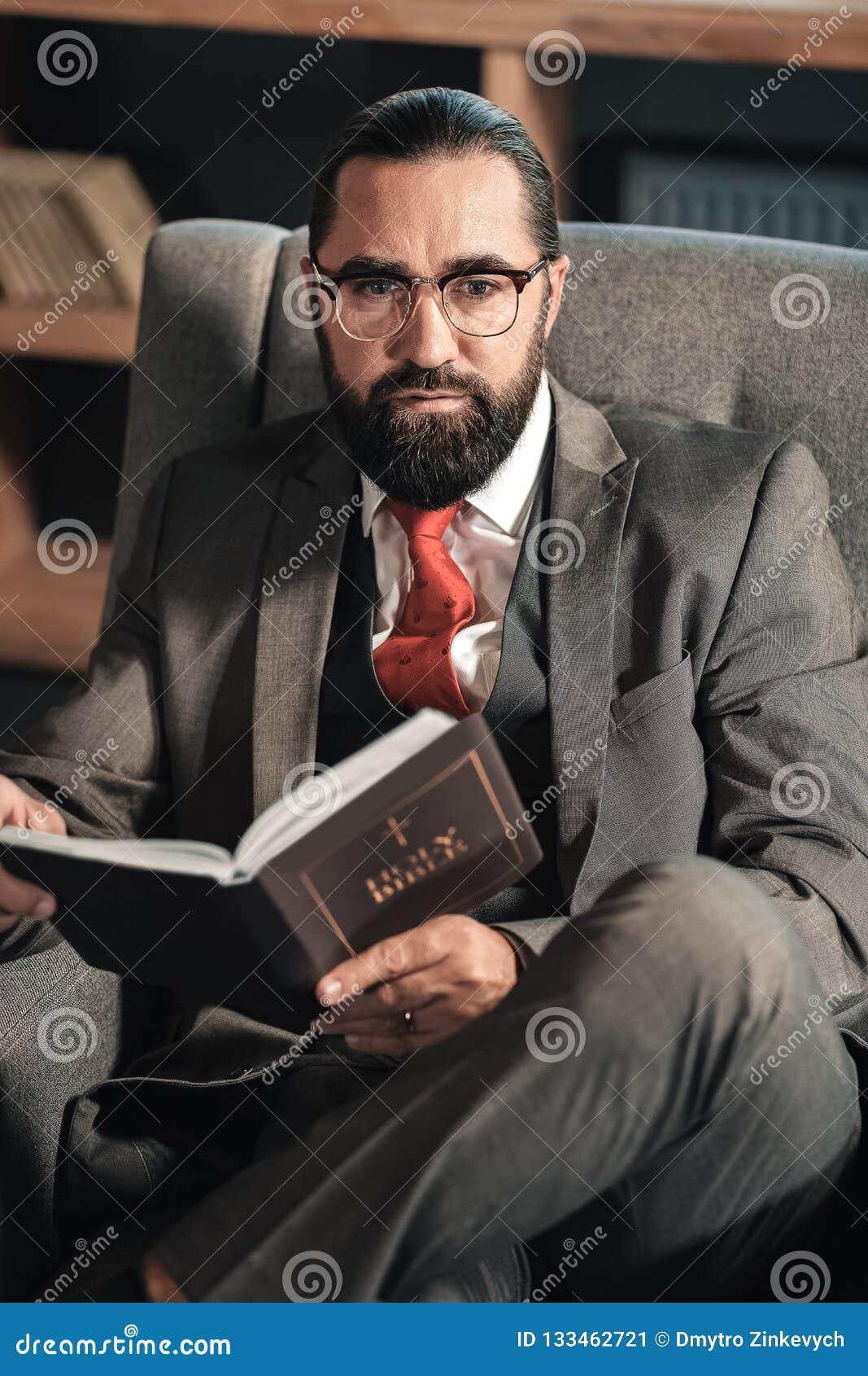 Sensación del hombre de negocios pensativa mientras que lee la biblia