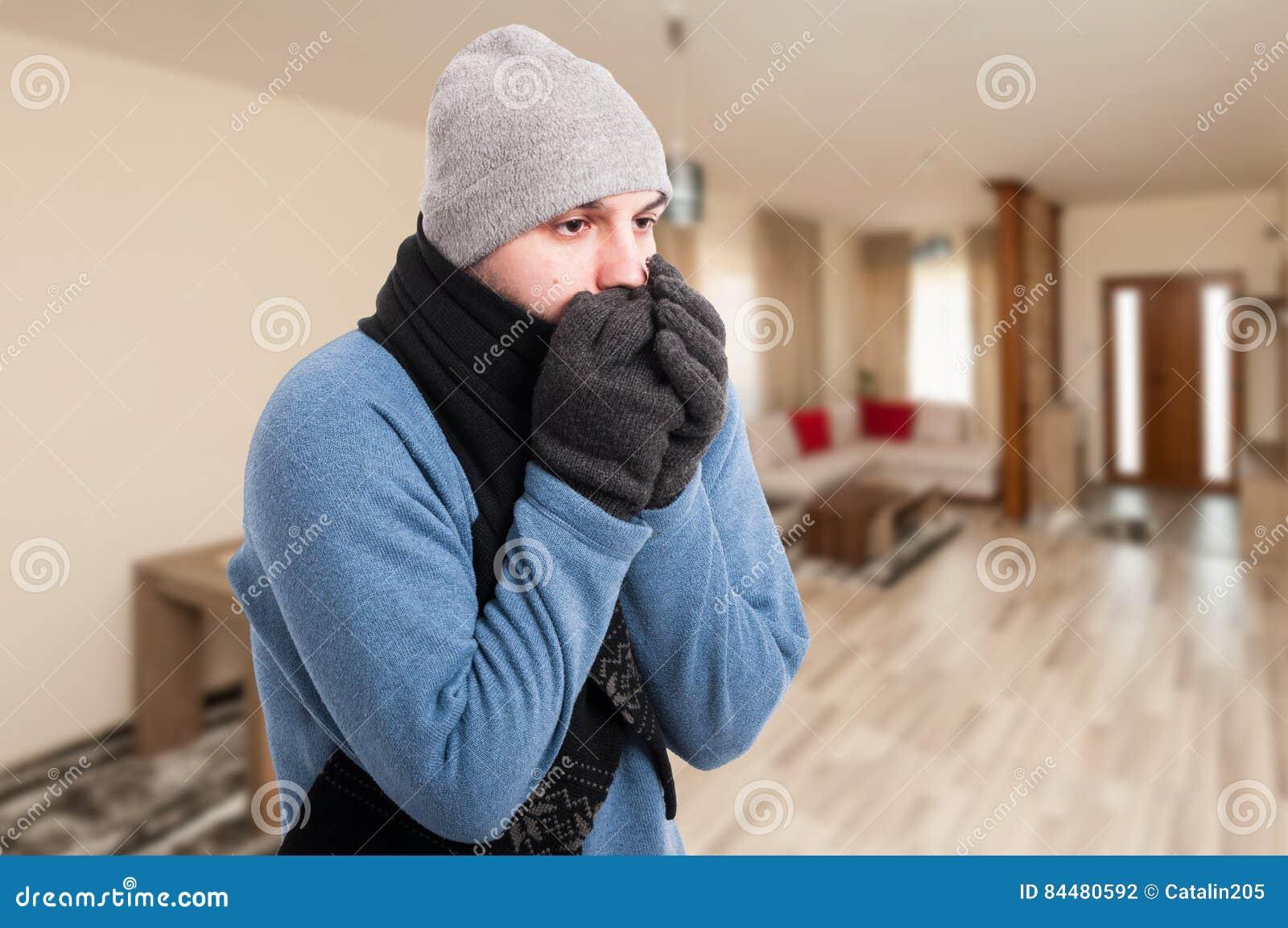 Sensación del hombre joven fría y que se calienta las manos