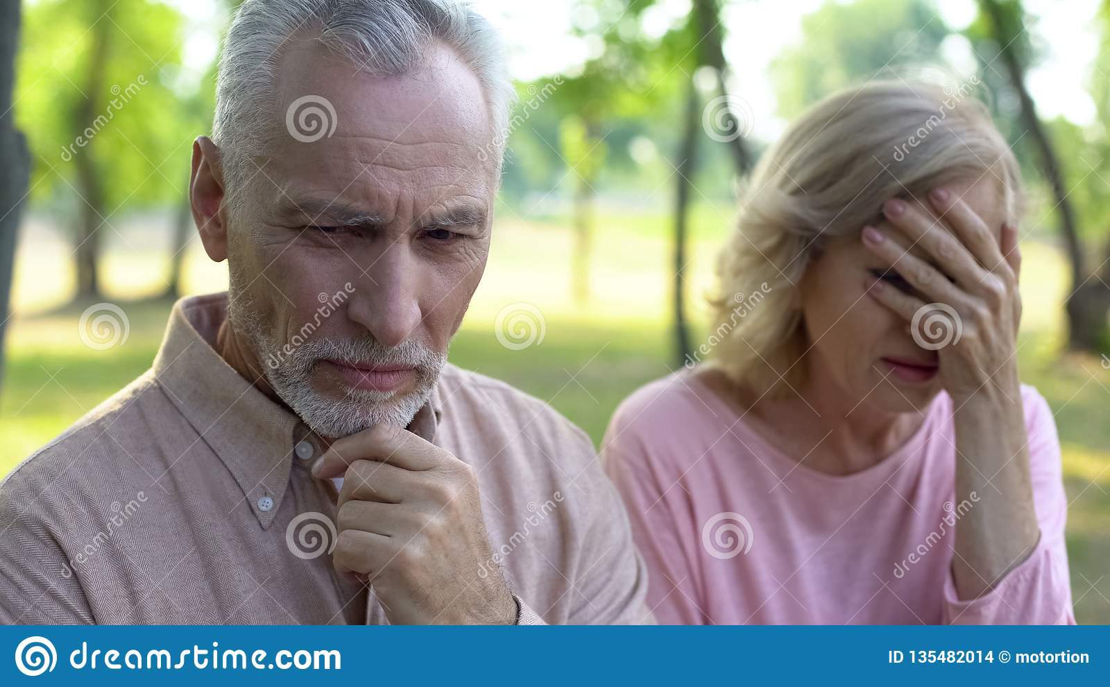 Sensación del hombre mayor triste y culpable, sentada gritadora de la esposa aparte, divorcio de los pares