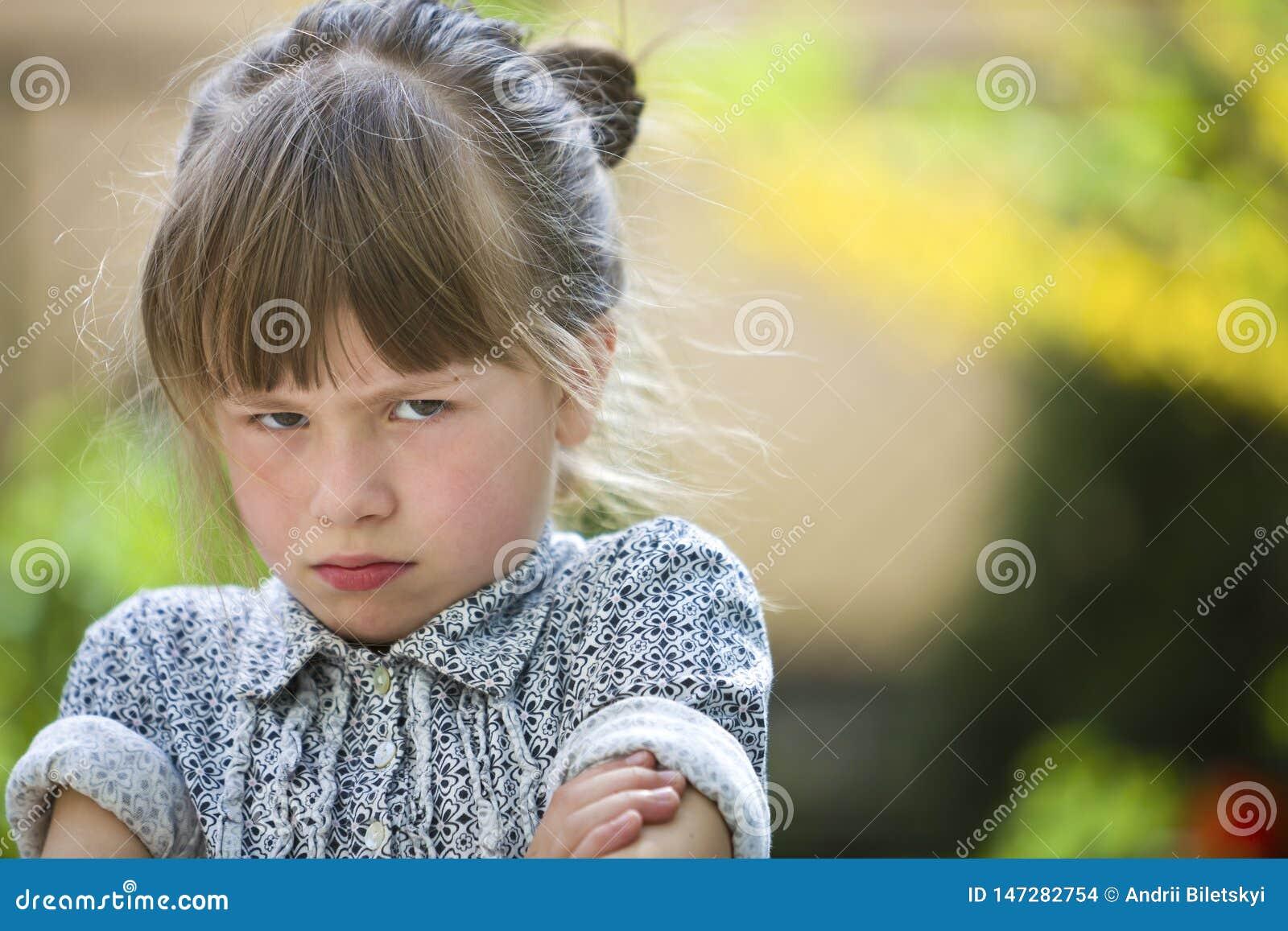 Sensibilità all aperto della ragazza lunatica divertente graziosa del bambino piccolo arrabbiata ed insoddisfatta sul fondo vago