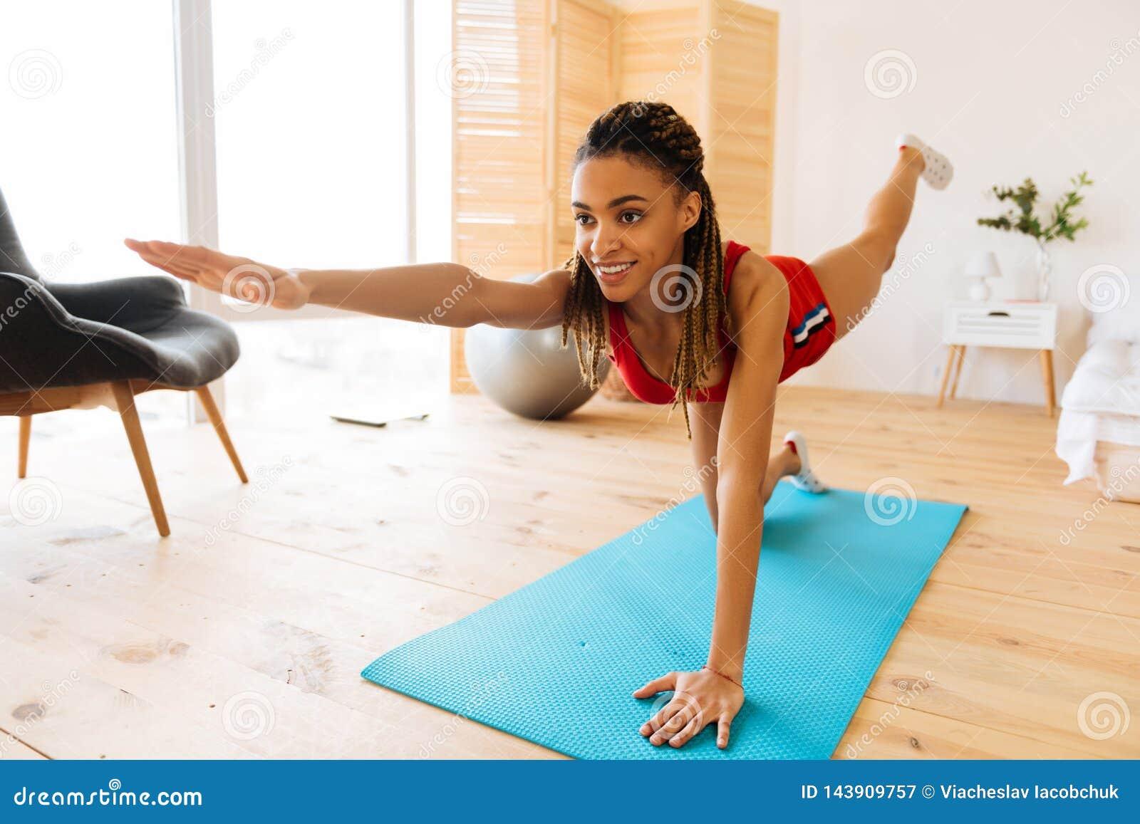 Sensibilità della donna allegra e stimolata mentre facendo yoga a casa