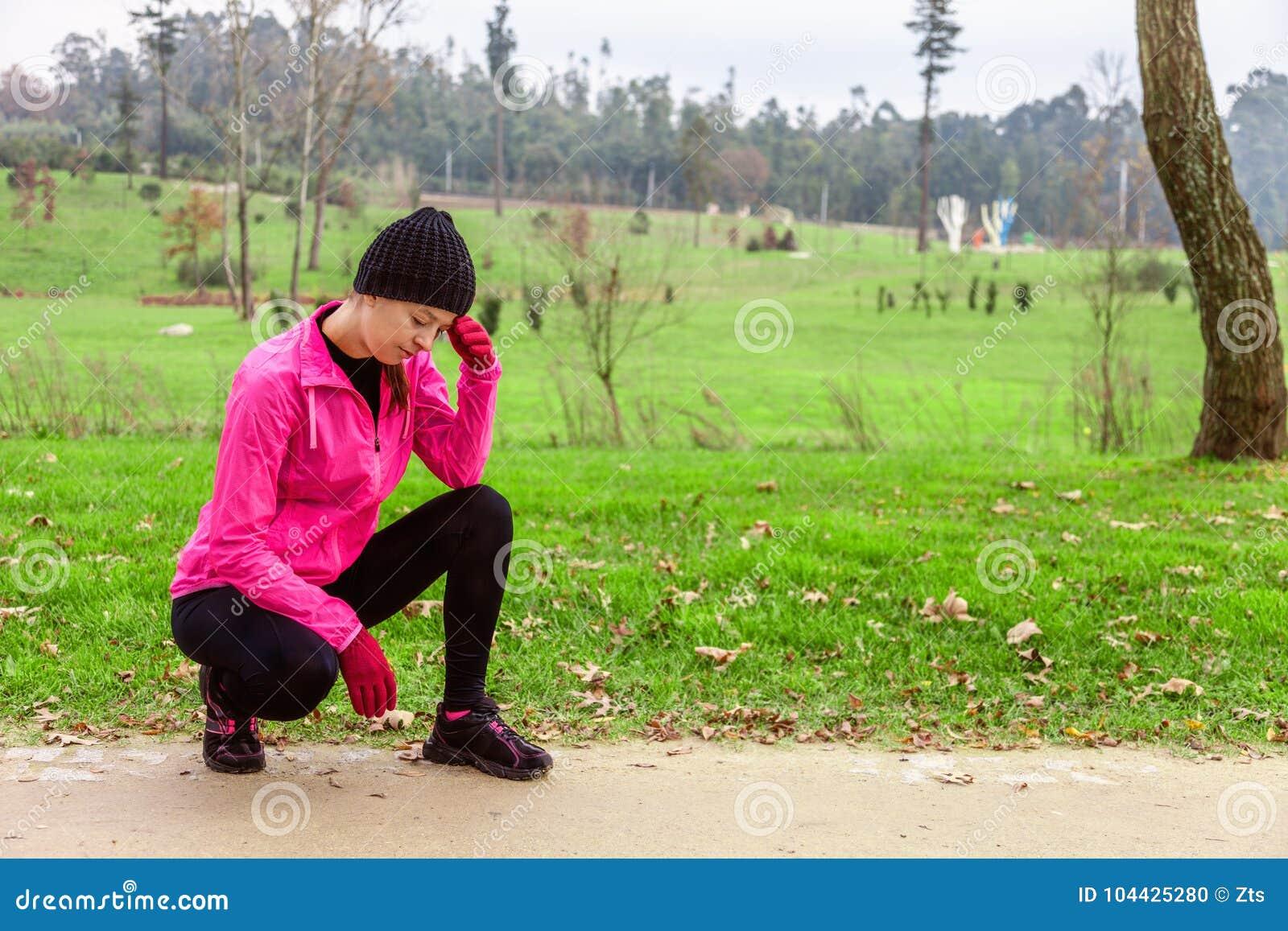 Sensibilità della giovane donna lightheaded o con l emicrania dopo il treno un giorno di inverno freddo sulla pista di addestrame