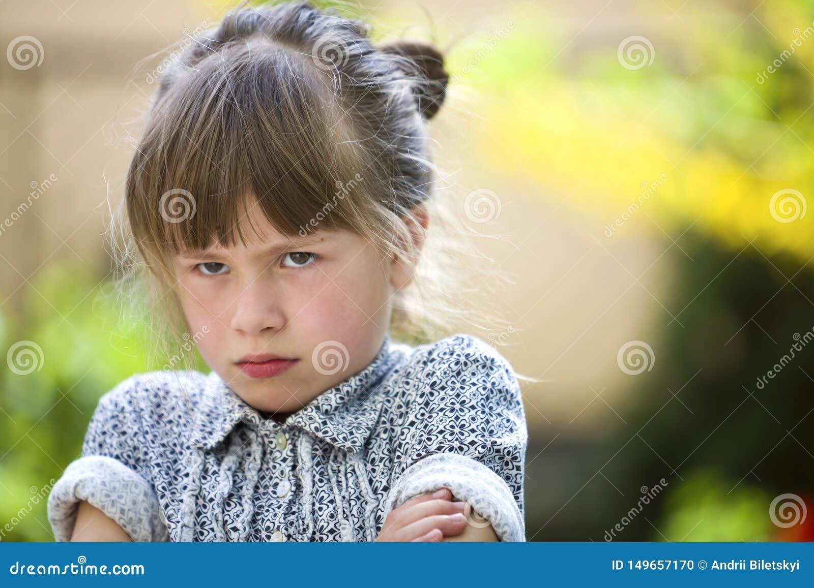 Sensibilit? all aperto della ragazza lunatica divertente graziosa del bambino piccolo arrabbiata ed insoddisfatta sul fondo vago
