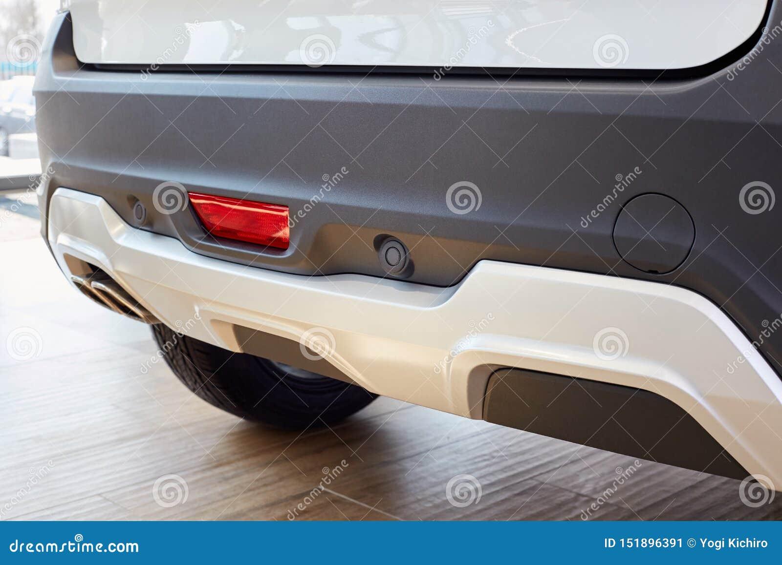 Sensores que parquean en un coche blanco, el parachoques trasero con el reflector y el tubo de escape y el lugar para instalar el