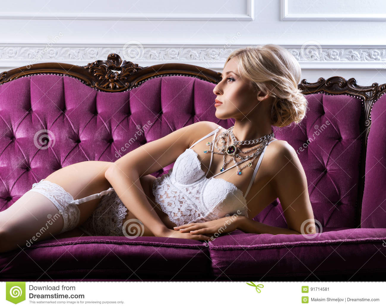 32e079233 and beautiful young girl in a bridal lingerie posing on a pink retro sofa.  Fashion