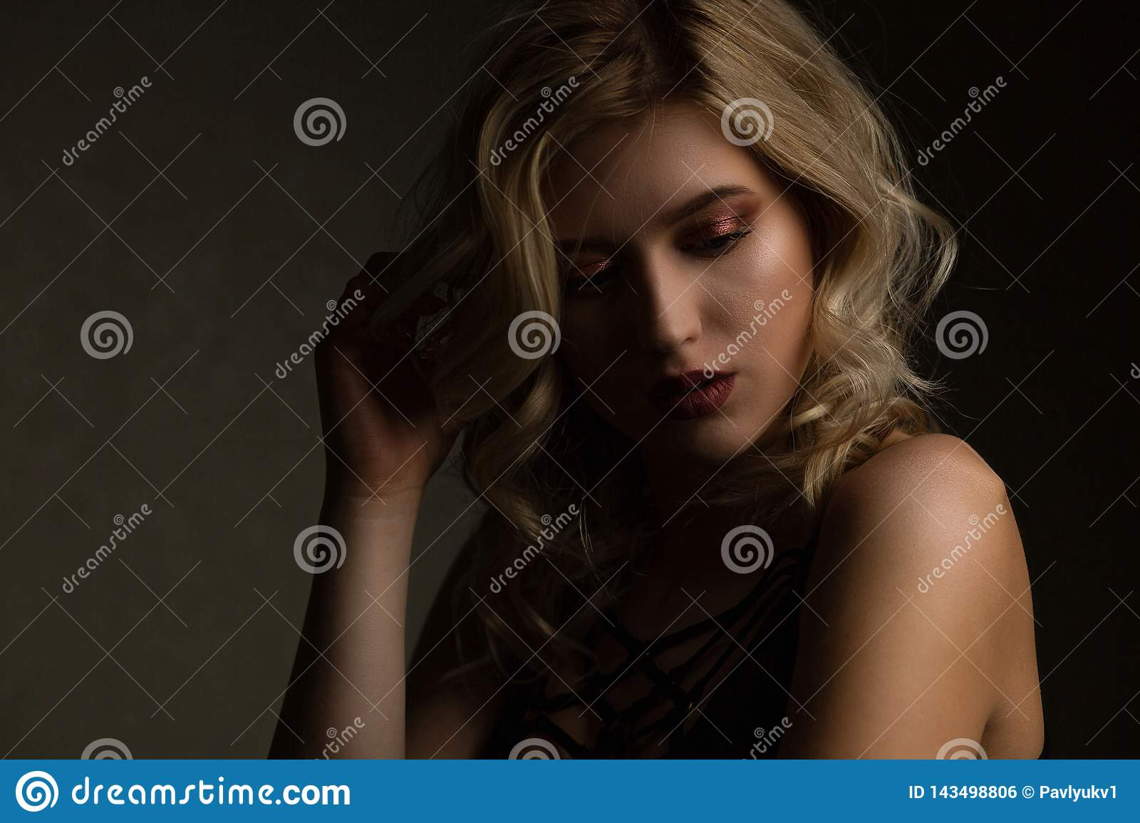 Sensual blonde model with perfect makeup and naked shoulders posing with contrast light. Empty space