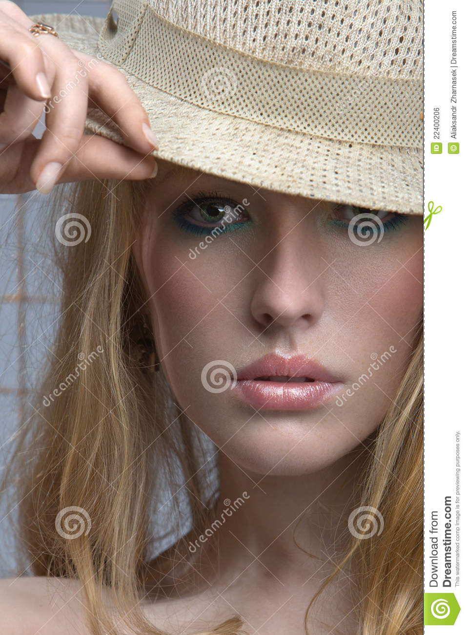Sensual blonde woman peers out from under the brim