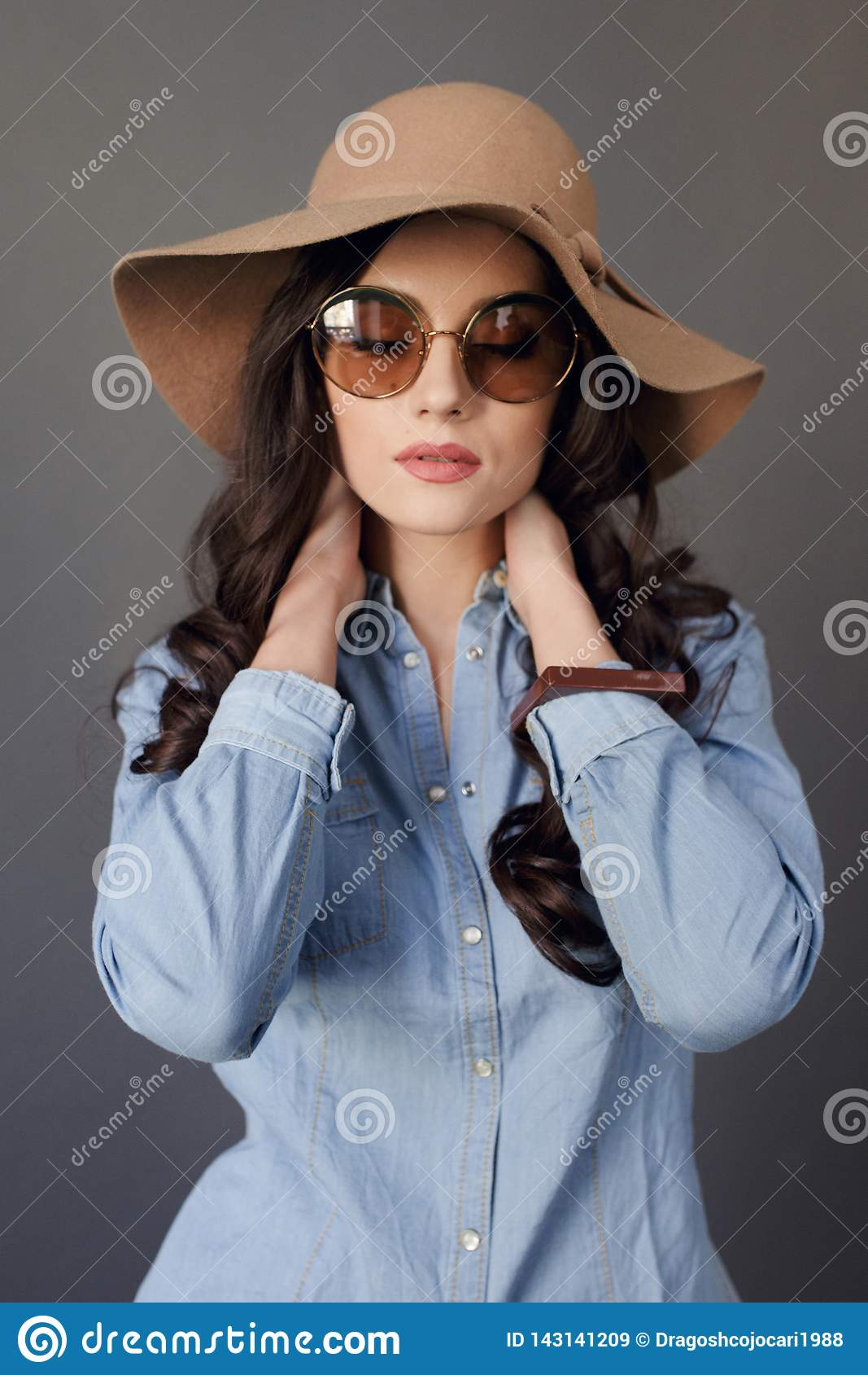Sensual brunette model with round sunglasses, curly hair, wearing in jeans shirt and beige hat, touches his neck.