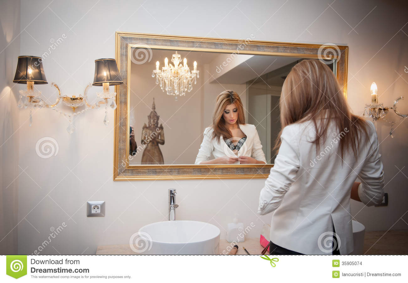 Sensual elegant woman in office outfit looking into a for Looking for mirrors