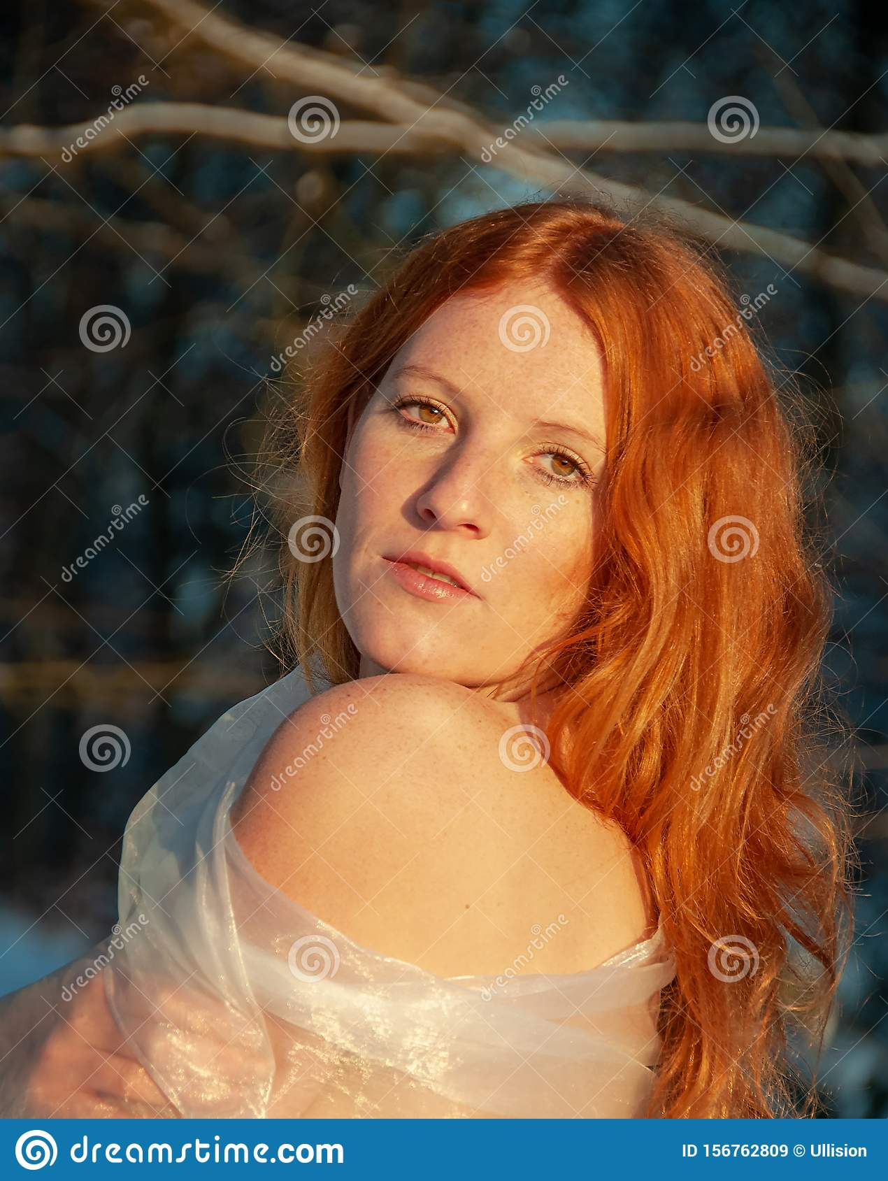 Sensual portrait of red-haired woman under the trees