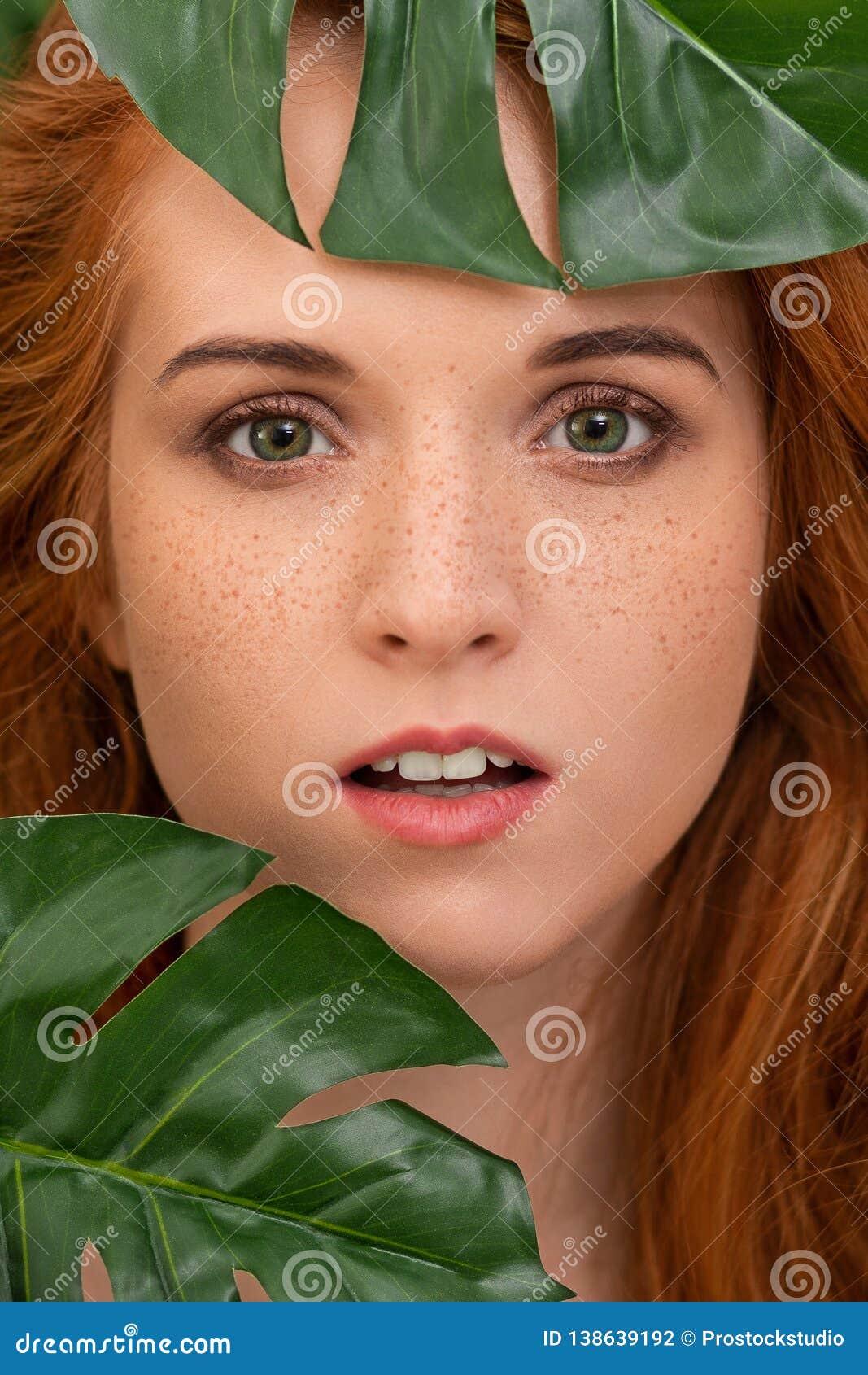 59f75fb64edfa Royalty-Free Stock Photo. Sensual portrait of redhead woman with green  leaves