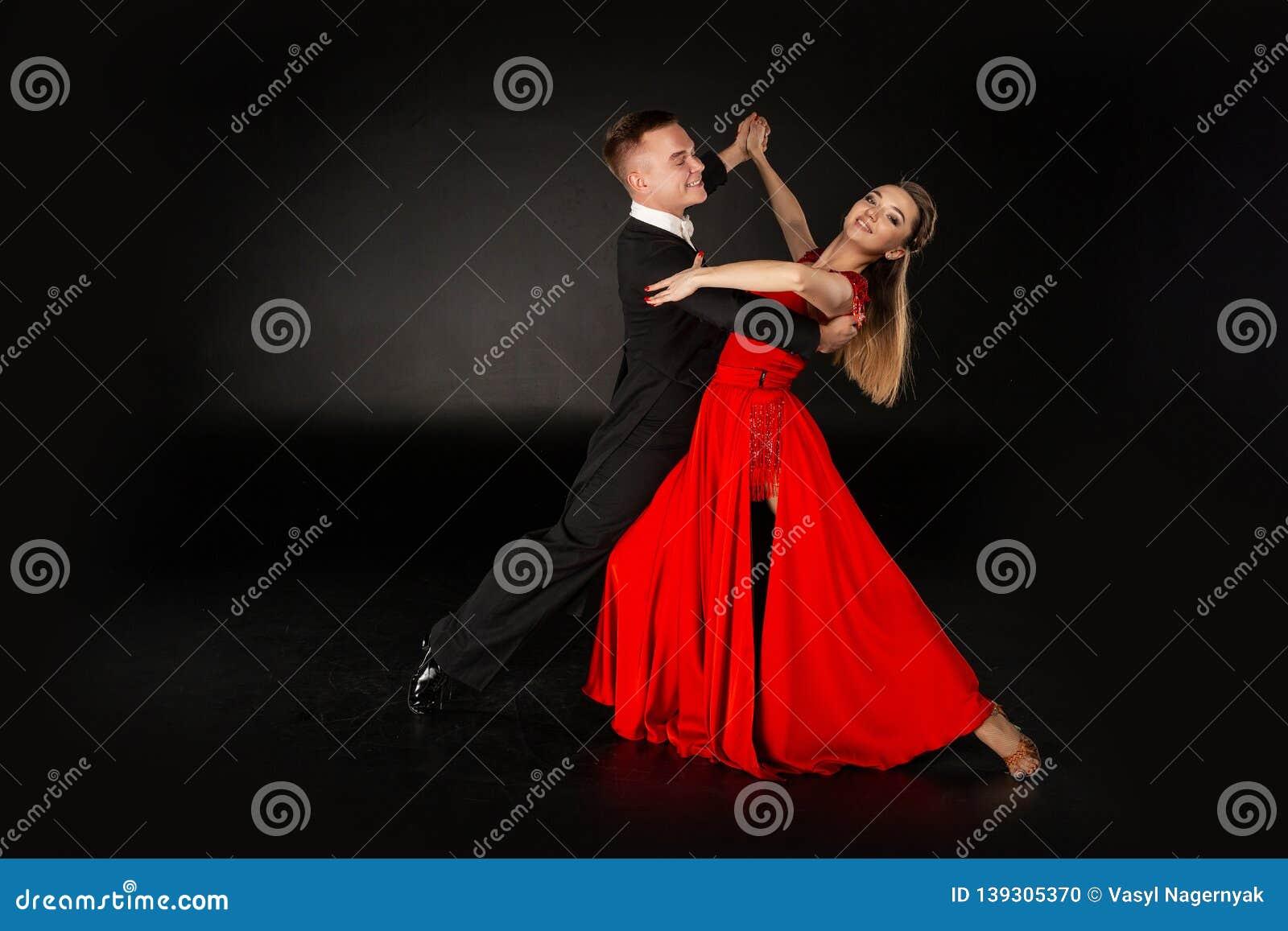 86f9b3e073d1b Sensual professional dancers dancing tango. Girl in red dress and men in  black suit. Studio shot on black background