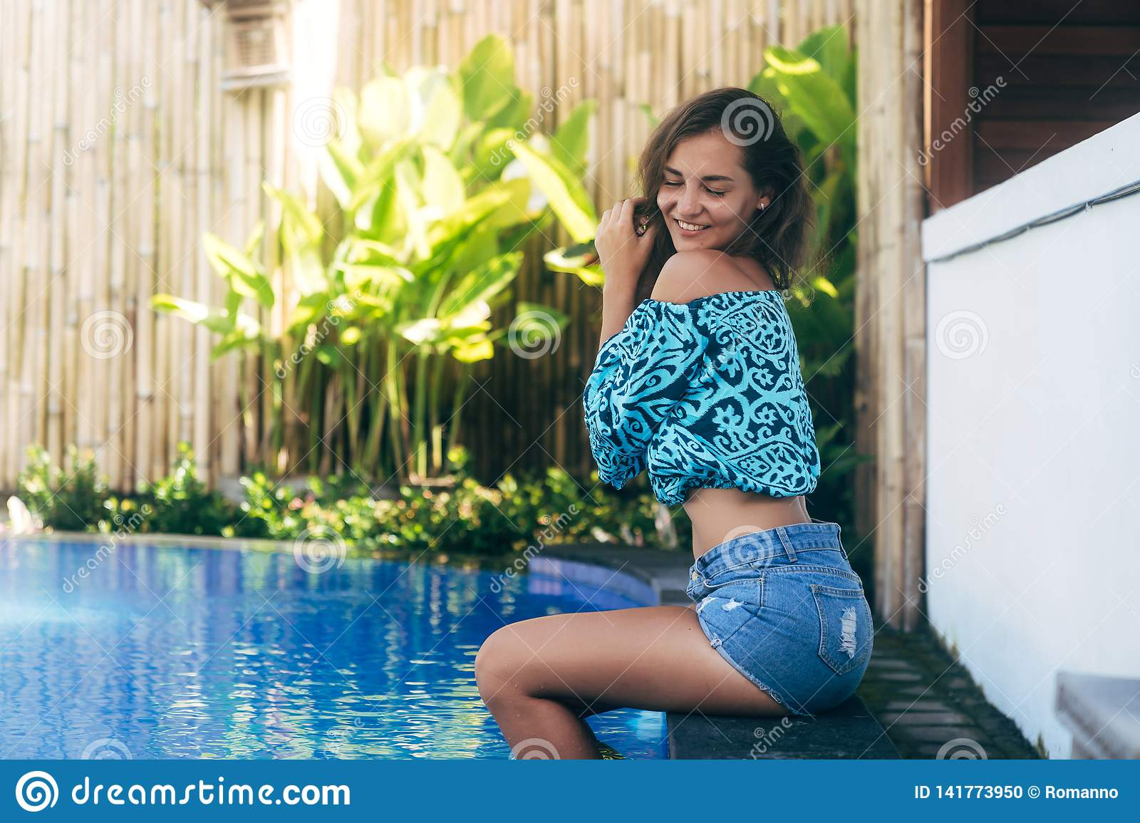 29dcbd513 Sensual girl in denim shorts and top sits on pool. Young tanned model  resting on