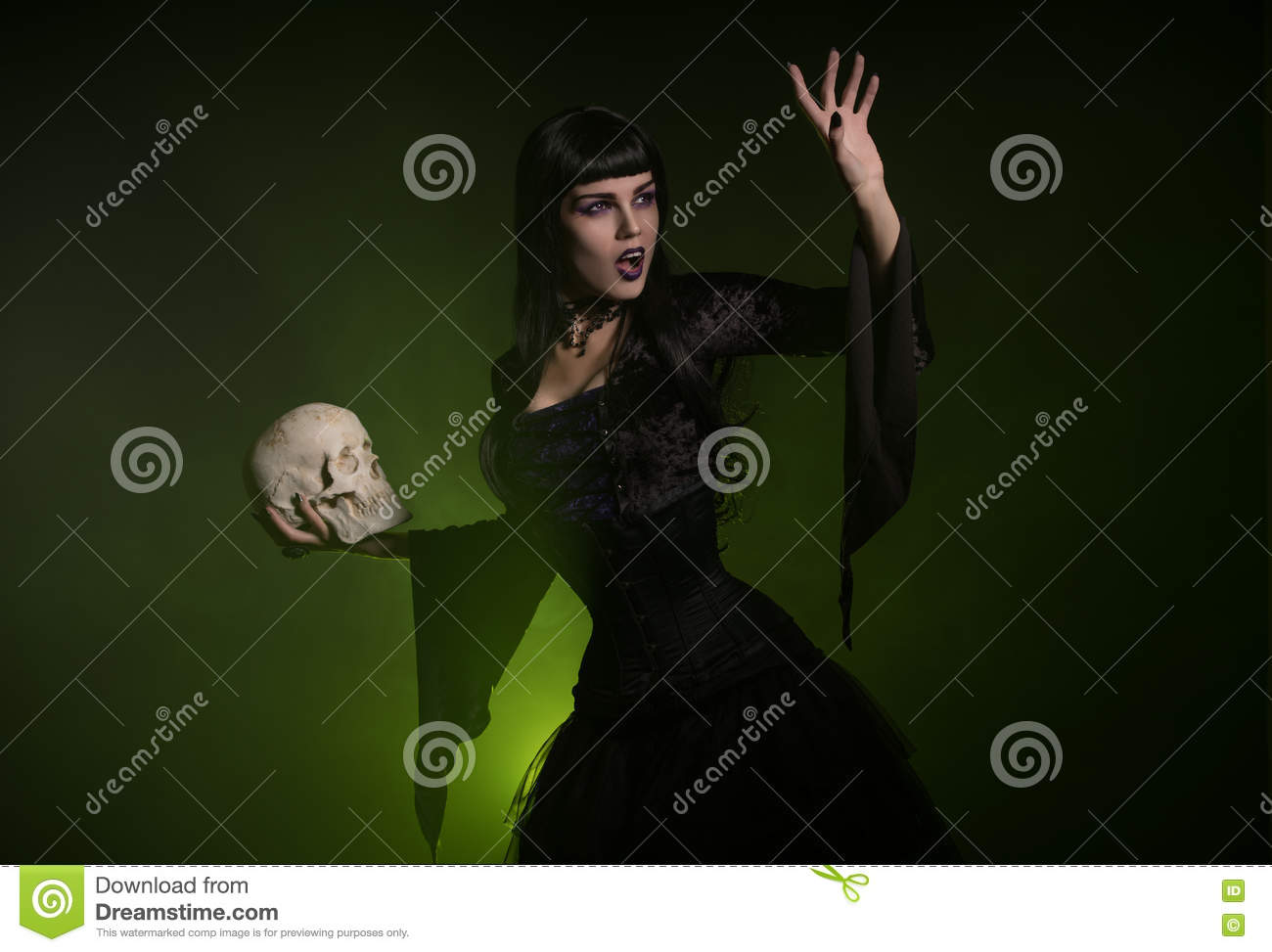 Sensual witch holding a skull in her hand