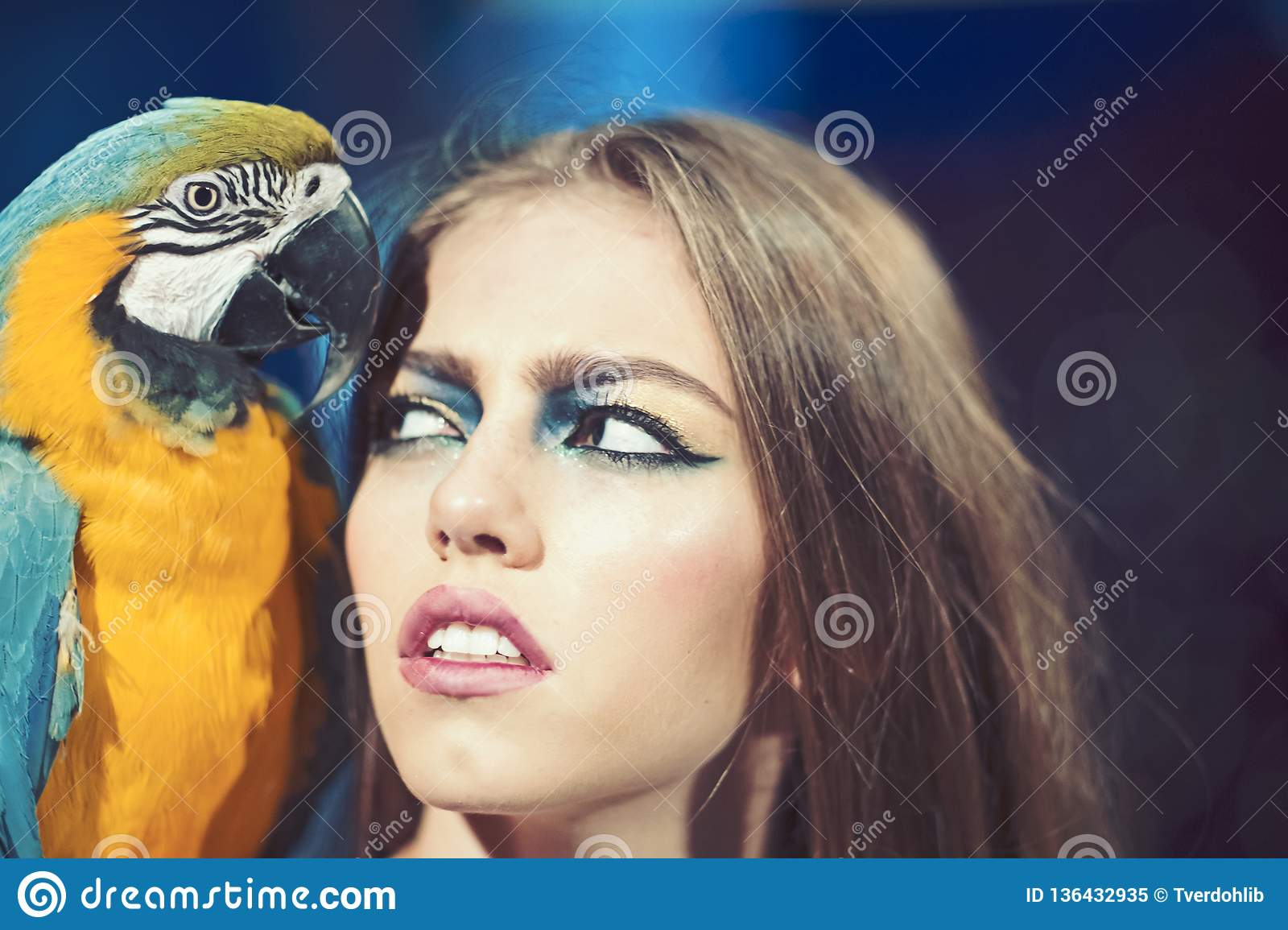 Woman with blue and yellow macaw. girl with makeup and bird pet. Beauty  model with exotic ara animal. Friends and friendship.