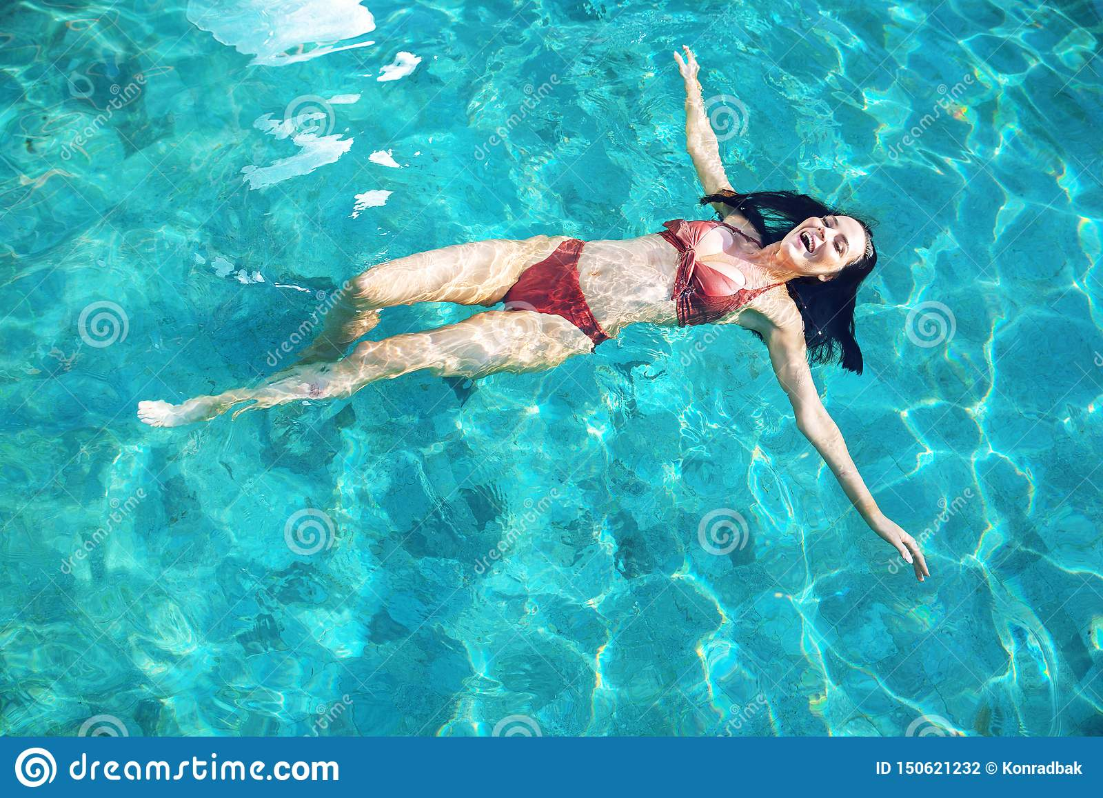 Sensual woman relaxing in the tropical, luxurious pool