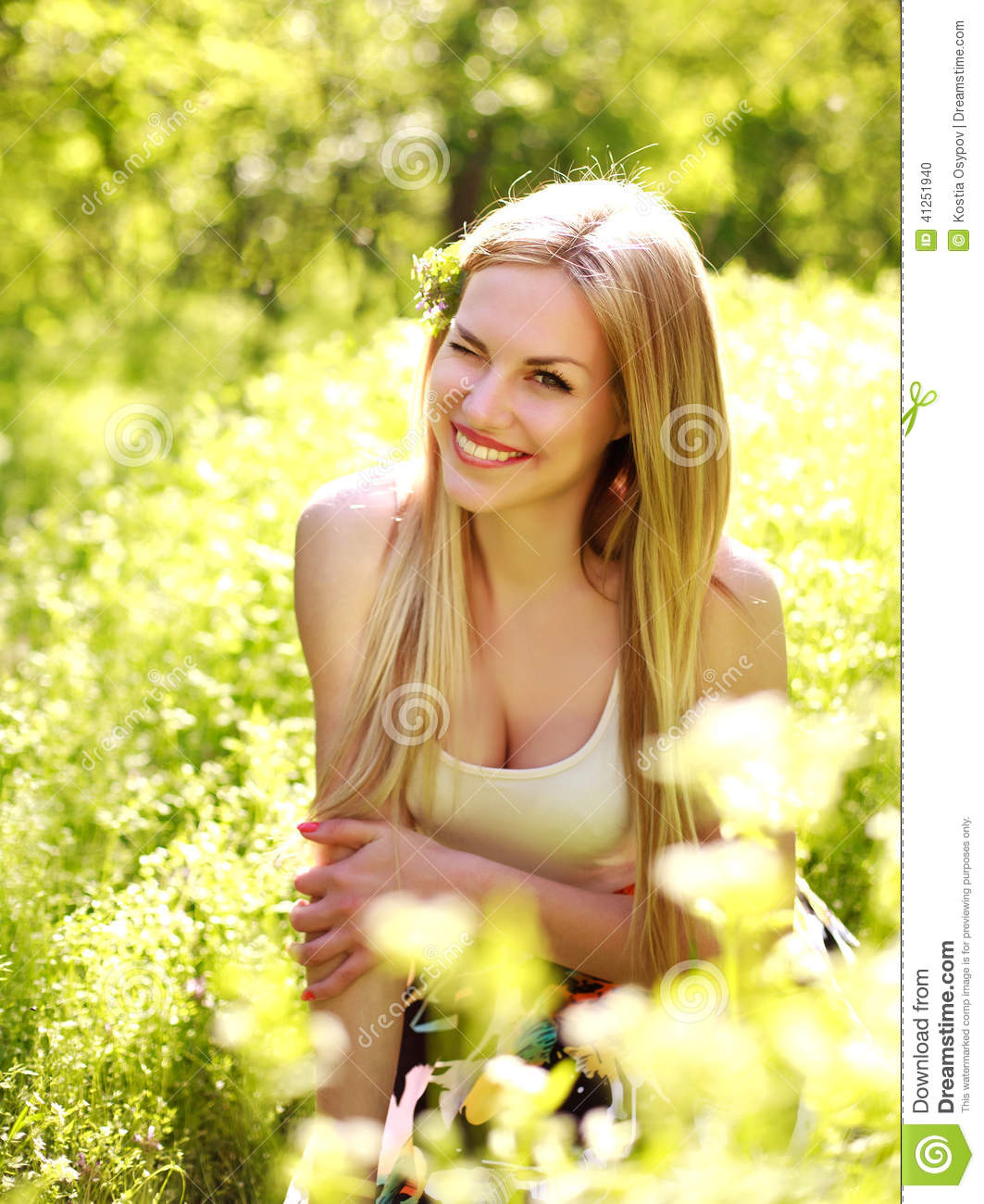 Sensual young woman, smiles sweetly in the flowered garden