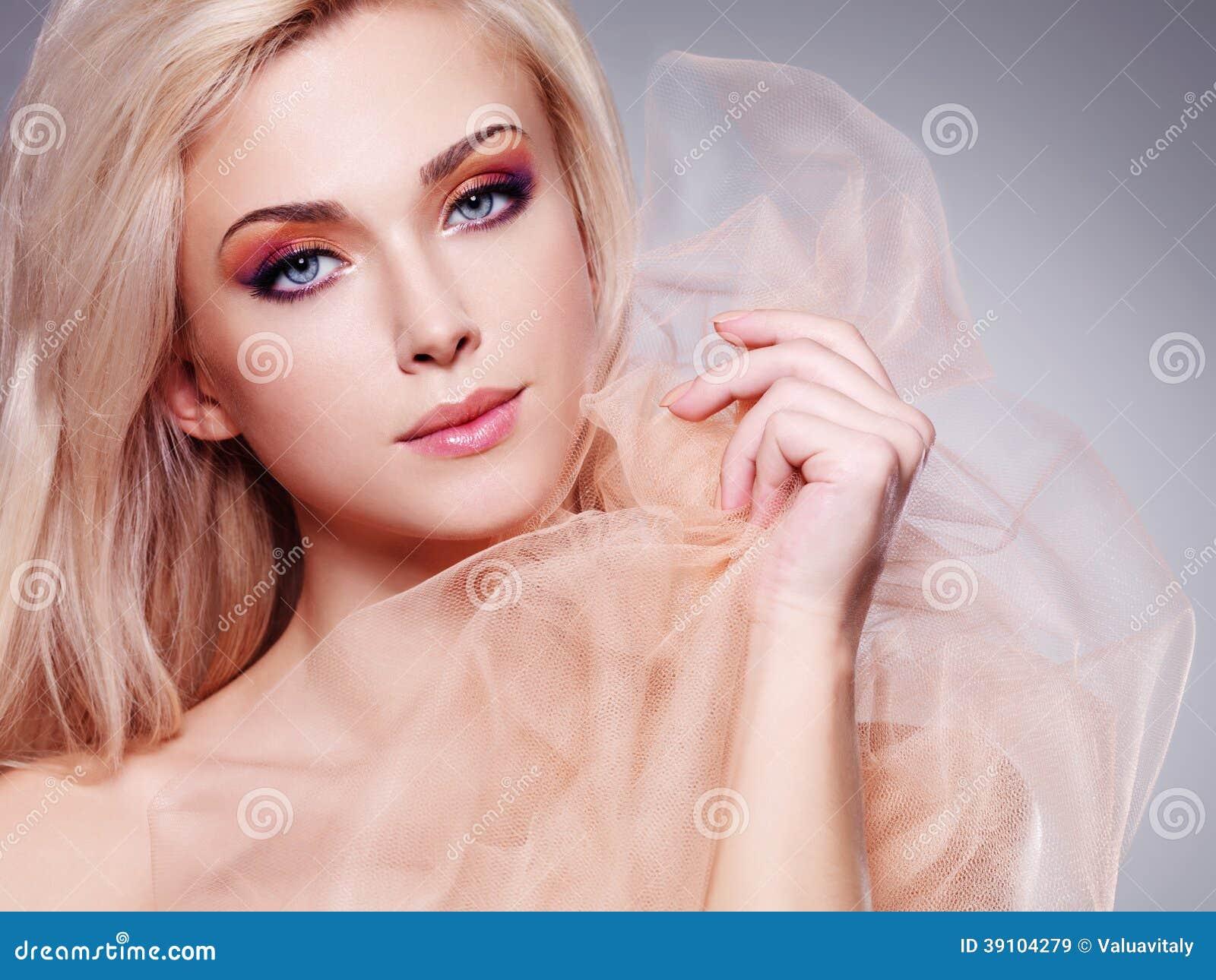 Sensuele blondevrouw die door beige behandelen.