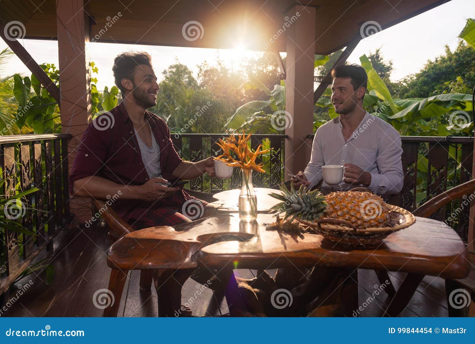 Sentada de dos mangos en la taza del control de la terraza del verano que desayuna que habla, individuos en café de consumición d